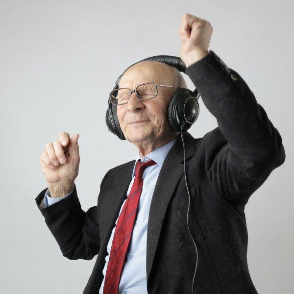 Homem idoso usa terno e ouve música com fones de ouvido