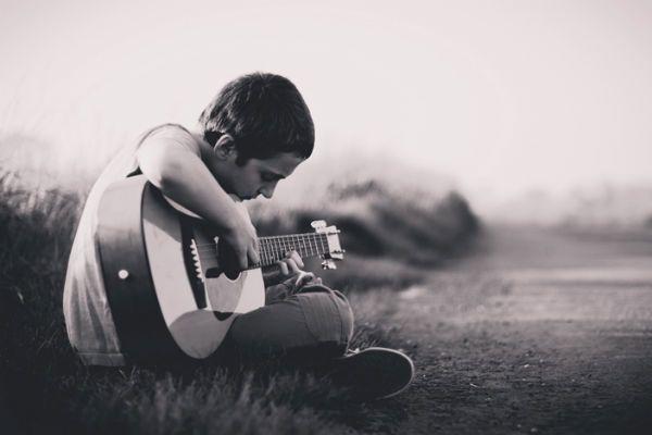 Menino toca violão