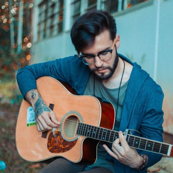 Rapaz tocando violão com dedicação e boa vontade