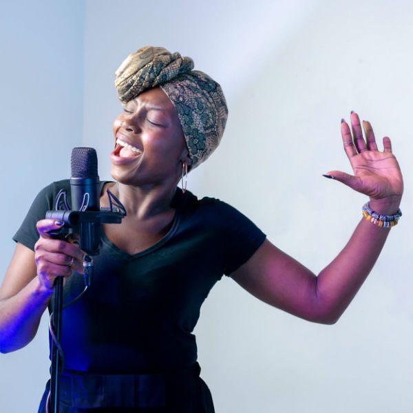 Cantora negra canta com um microfone profissional