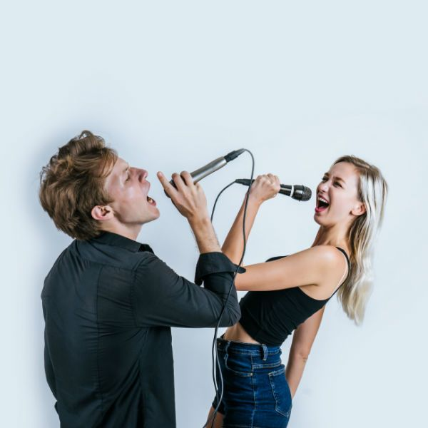 Homem e ulher, ambos jovens, cantam com microfone nas mãos