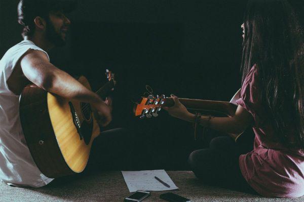 Rapaz e moça tocam violão