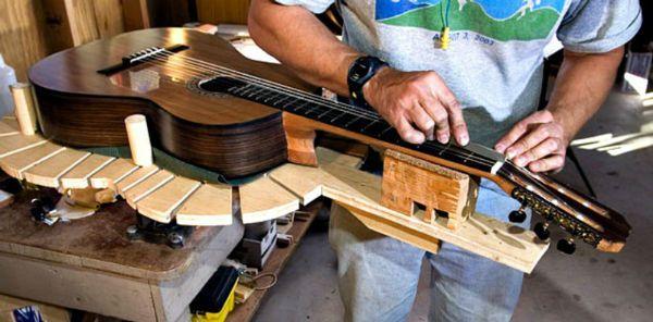 Luthier trabalha no braço de um violão