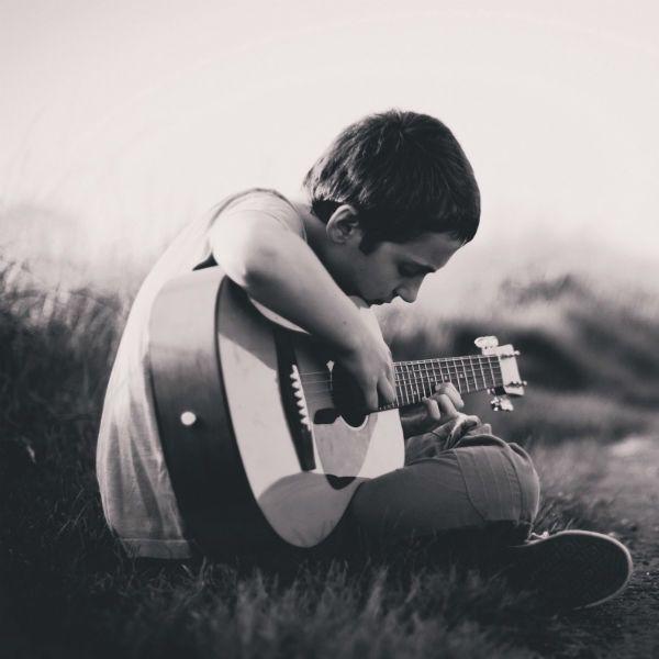 Sentado na grama, menino toca violão de nylon
