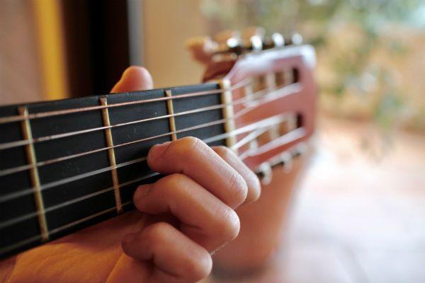 A mão de uma criança faz o acorde de ré menor em um viiolão com cordas de nylon