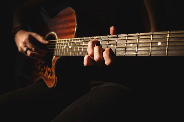 Músico toca em violão de aço e desempenado