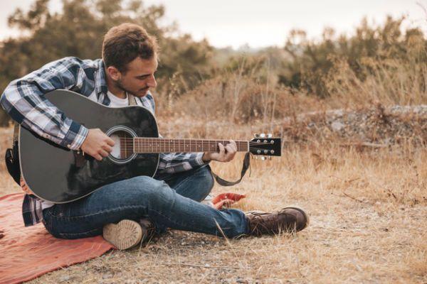 Rapaz faz acorde complexo no violão