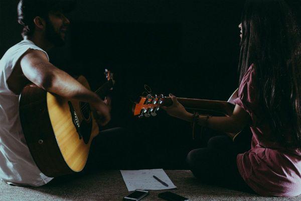 Rapaz e moça estudam violão juntos
