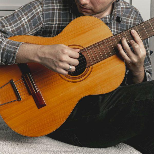 Homem jovem toca violão clássico