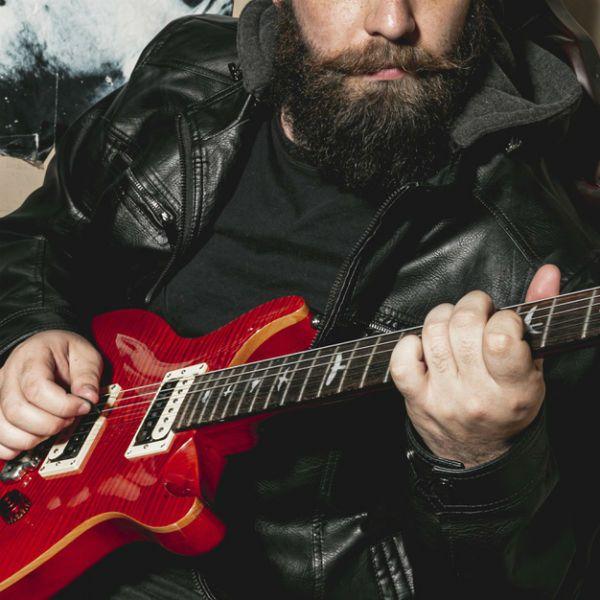Guitarrista barbudo toca acordes em uma guitarra vermelha