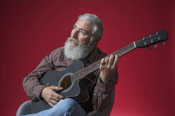Músico veterano e experiente toca violão