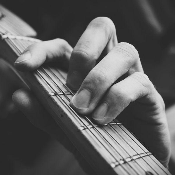 Guitarrista faz o acorde de Fá Maior, com pestana