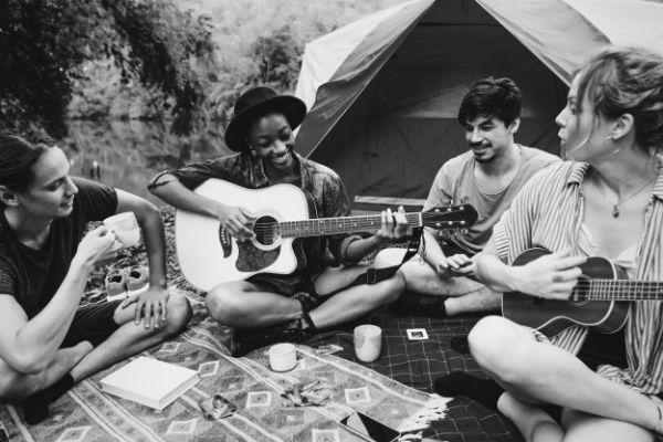 Jovens tocam violão e cantam durante acampamento