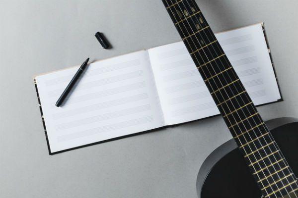 Caderno de música, violão e caneta: material de estudo musical