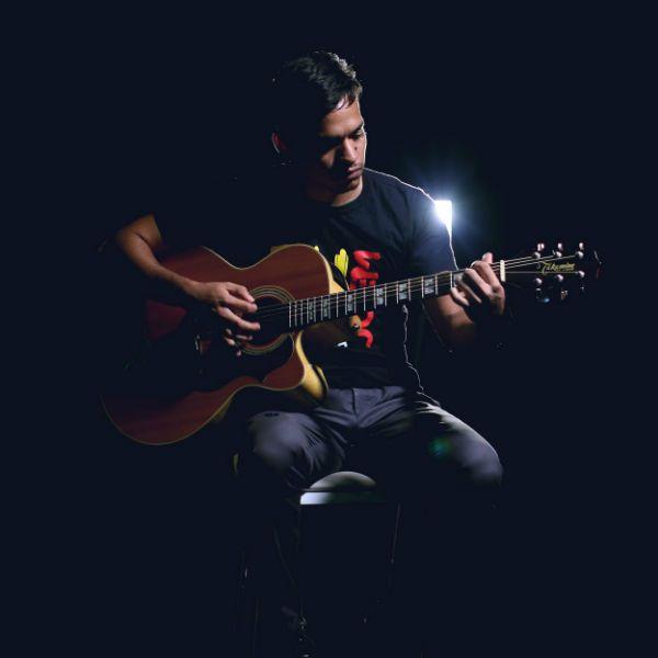 Músico iniciante toca violão em um ambiente de pouca luz