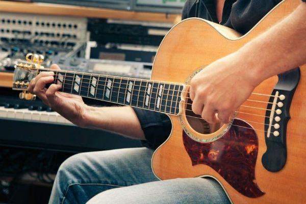 Músico canhoto toca violão com as mãos invertidas