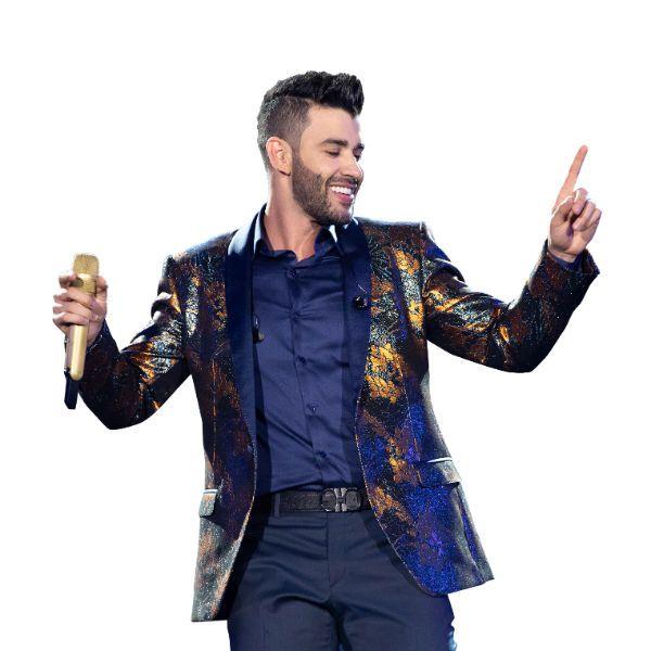 Gusttavo Lima segura o microfone e se diverte durante apresentação ao vivo