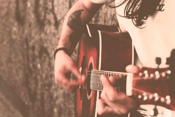 Rapaz cabeludo e tatuado tocando violão
