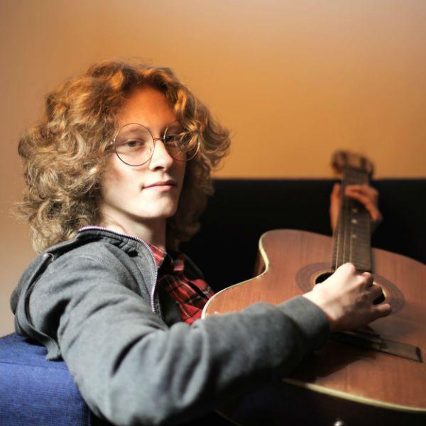 Sentado no sofá, jovem faz acordes simples no violão