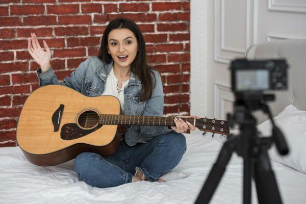 Jovem mulher gravando vídeo de como tocar violão