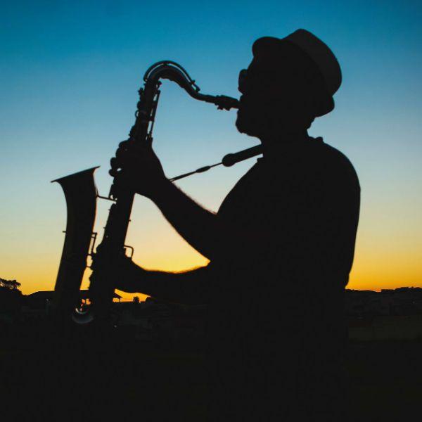 Silhueta de homem tocando saxofone com um belo pôr do sol ao fundo