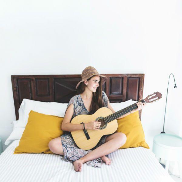 Mulher jovem, de vestido e chapéu, sentada na cama tocando violão