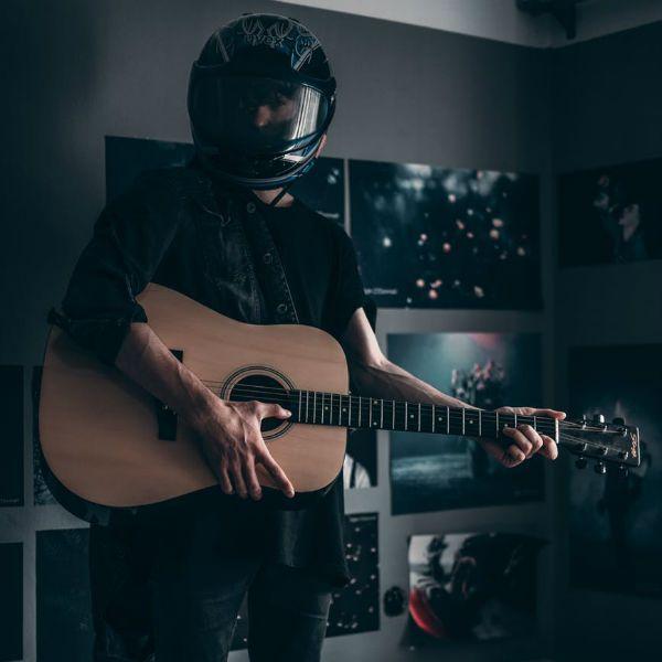 Músico usa capacete, botas e segura seu violão