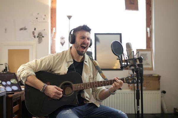 Músico toca violão e canta, em um home studio