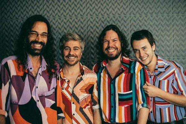 Integrantes da banda Maglore, decamisas coloridas, posam em um estúdio