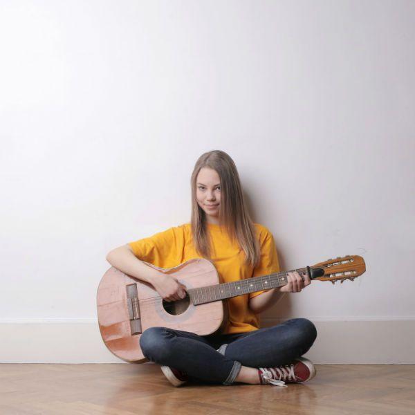 Mulher jovem, sentada no chão, tocando violão