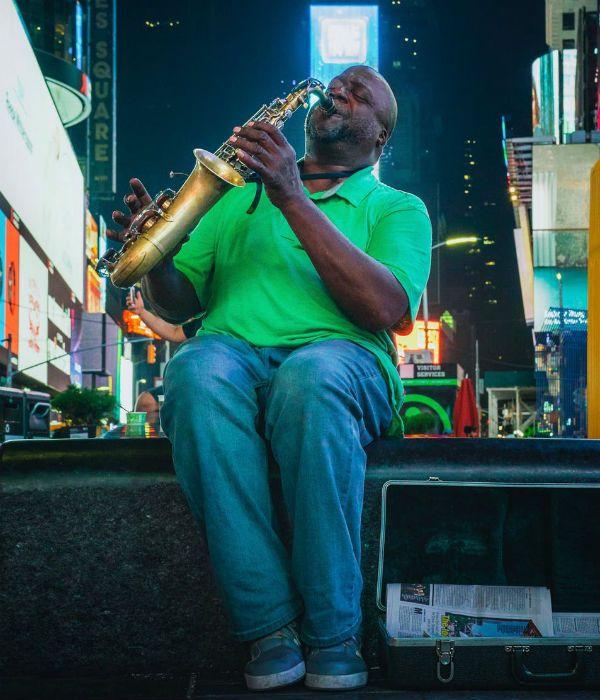Homem negro, gordo e mais velho toca saxofone, sentando em um banco de praça