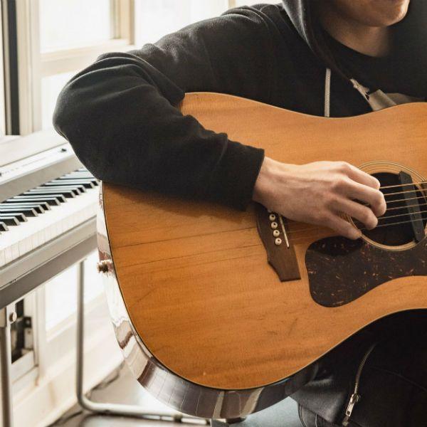 Jovem sentado no banco de um home studio toca violão. Atrás dele, há um teclado