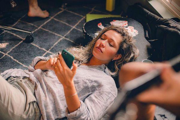 A cantora Lorena Chaves deitada, com telefone em mãos, no périodo de isolamento social