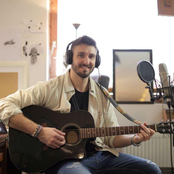 Músico em home studio, tocando violão e com fones de ouvido