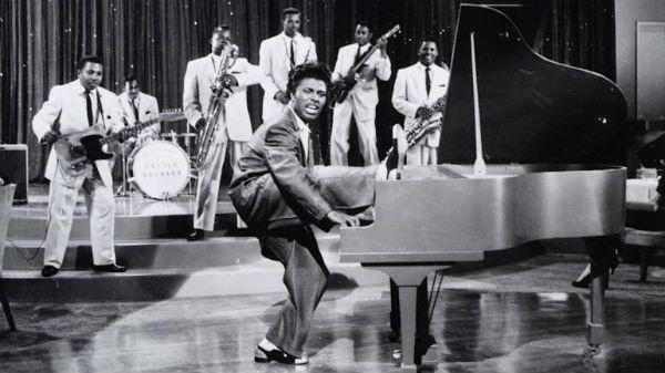 Um jovem Little Richard tocando piano e com uma das pernas sobre o instrumento