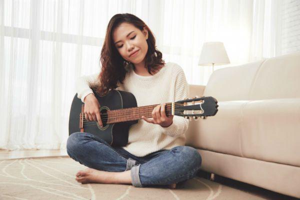 Menina com traços asiáticos, sentada no chão da sala e tocando violão