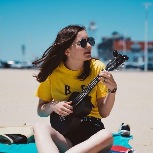 Garota toca ukulele na praia; o isntrumento está na posição correta