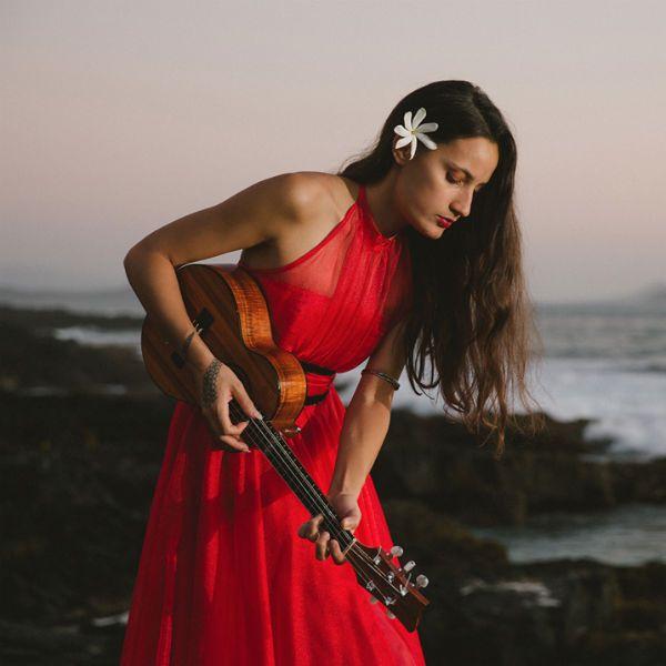 taimane gardner toca ukulele, de costas pro mar, de vestido vermelho