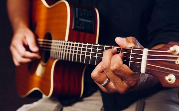 Músico faz o acorde de dó maior no violão de cordas de aço