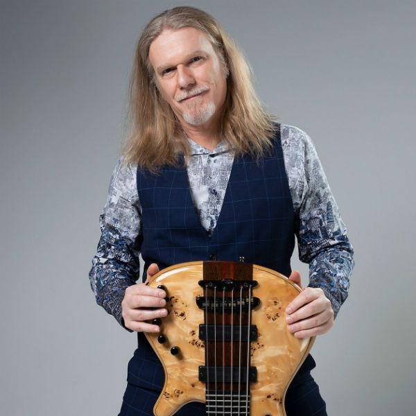 De pé, o músico Humberto Gessinger seguro um baixo de seis cordas virado de ponta à cabeça