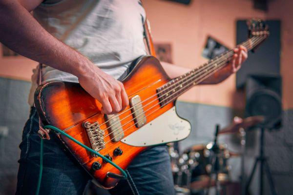 Baixista toca com baixo de quatro cordas, modelo firebird
