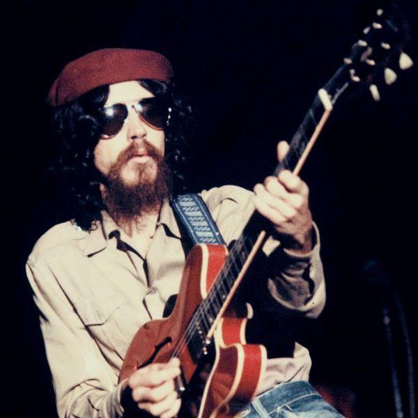 Raul Seixas usa sua tradicional boina cor de vinho e toca sua guitarra semi acústica vermelha
