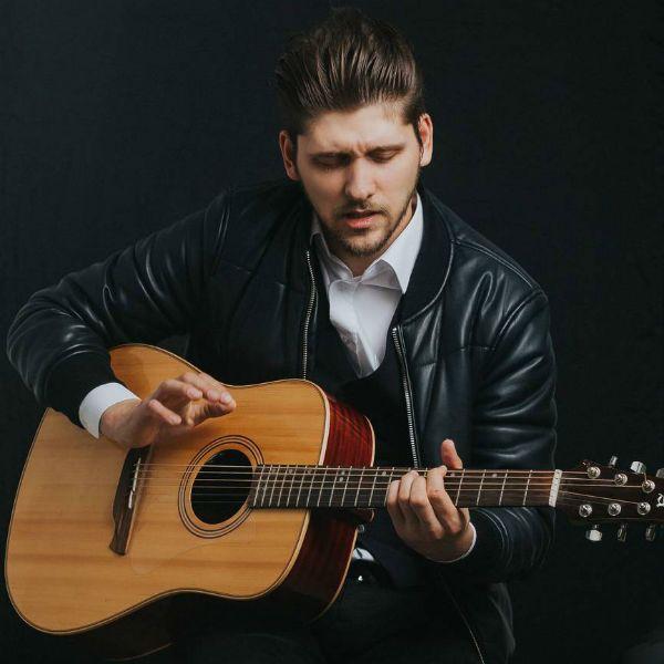 Homem sentado toca violão com a écnica fingerstyle