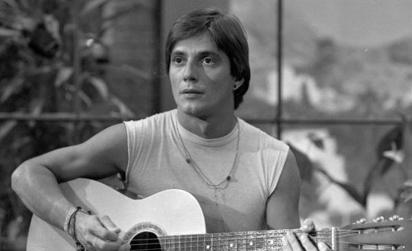 Um ainda jovem Fábio Jr. tocando violão