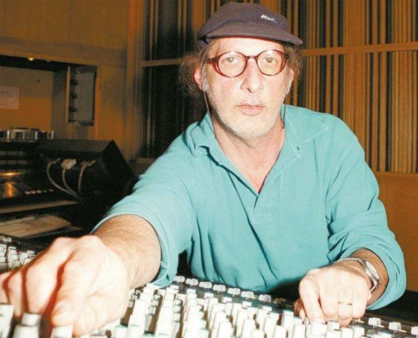 De boné e óculos, o produtor musical Arnaldo Sacomanni trabalha em uma mesa de som