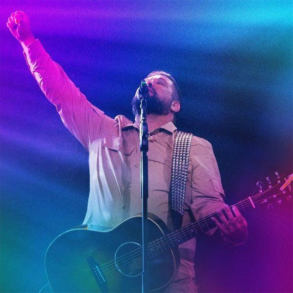 Fernandinho fecha os olhos e ergue o punho em reverência a deus, durante a gravação do DVD Santo