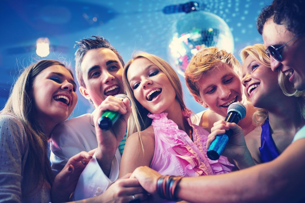 Grupo de amigos cantando com microfones