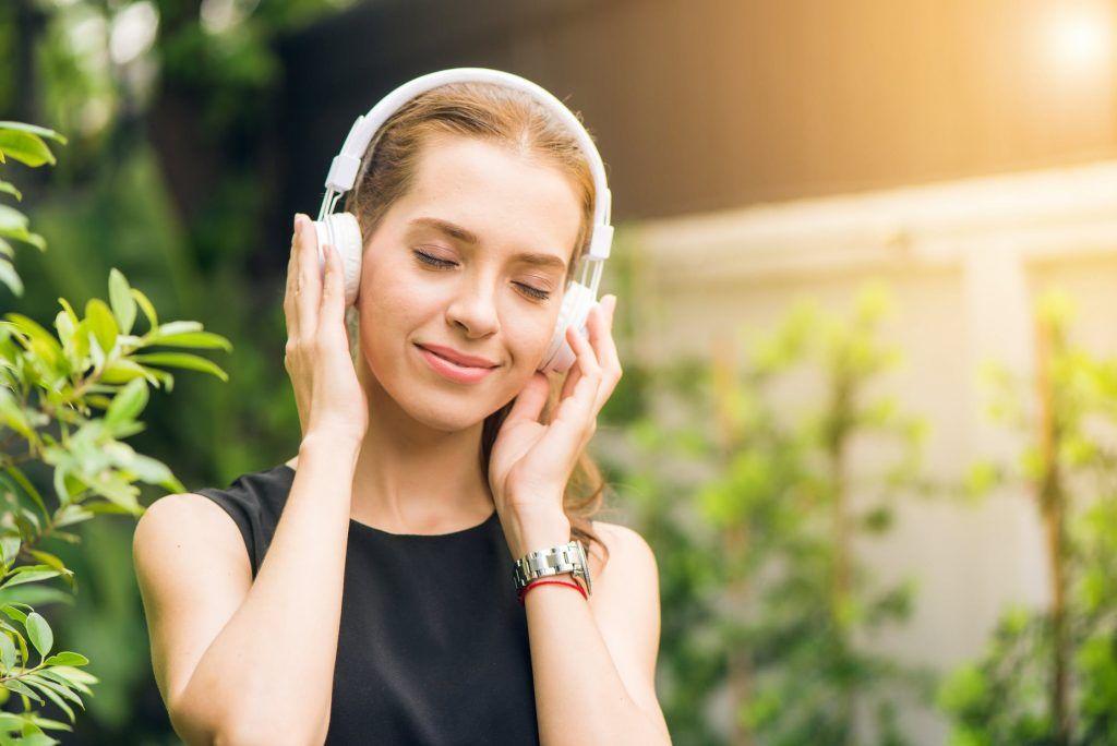 Mulher ouvindo música com fones de ouvido de olhos fechados