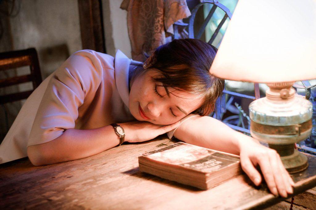 Mulher dormindo deitada em uma mesa