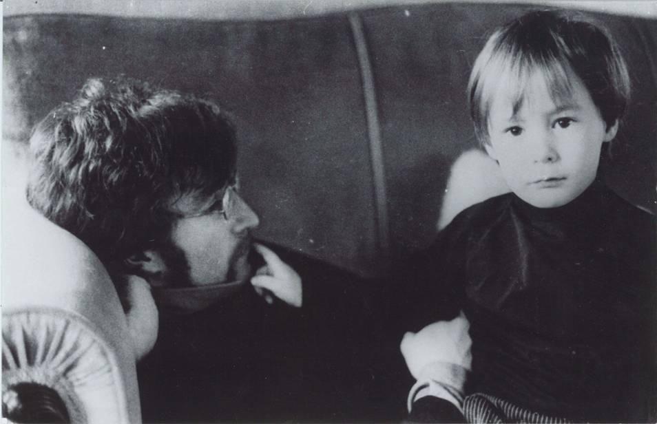 John Lennon e o filho Julian deitados em um sofá.